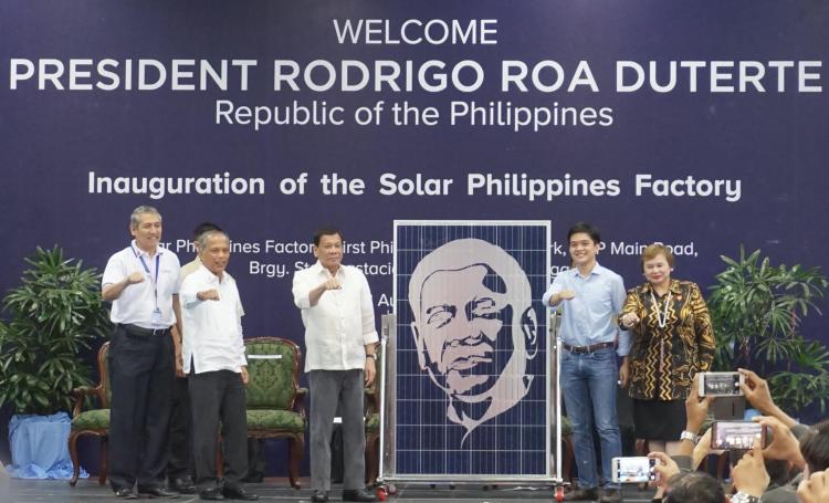 """Solar Philippines CEO Leandro Leviste presents a """"Duterte Edition"""" solar panel to President Rodrigo Duterte. Also on stage are DOE Secretary Alfonso Cusi, PEZA Director General Charito Plaza, and Solar Philippines COO Roy Oyco. Credit: Solar Philippines"""