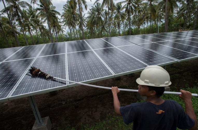 An employee of PT Perusahaan Listrik Negara (PLN) cleans the surface of solar panels at a solar power generation plant in Gili Meno island photo taken by Antara Foto