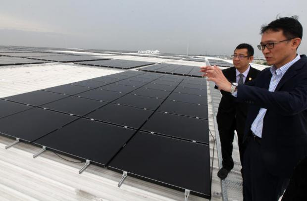 Curtis Ku (front), senior business director of Delta, takes Yossapong Laoonual, president of the Electric Vehicle Association of Thailand, to visit Delta's solar rooftop in Bangpoo Industrial Estate. THITI WANNAMONTHA Bangkok Post