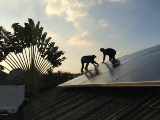 Workers install solar panels on a house, which can help residents cut down on their electricity bills. WEERABOON WISARTSAKUL